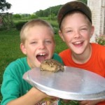 Silly boys catching toads off Grandma's porch